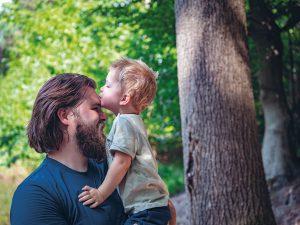 kind geeft man kus op hoofd